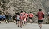Un grupo de corredores haciendo la maratón de Mendoza, paisaje de montañas
