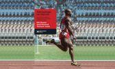 Es un corredor entrenando, vestido de rojo en una pista de atletismo