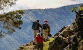 Tres personas subiendo una montaña , con una paisaje de otra montaña atrás