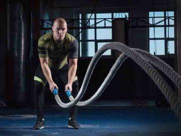 Hombre entrenando con cuerdas, crossfit