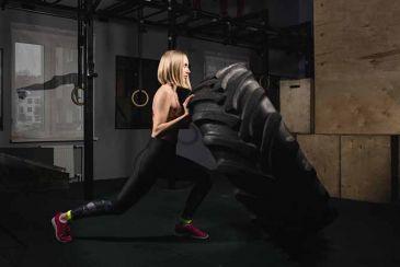 Mujer entrenando con una llanta, crossfit