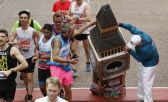 Bates vestido de Big Ben durante la maratón siendo ayudado